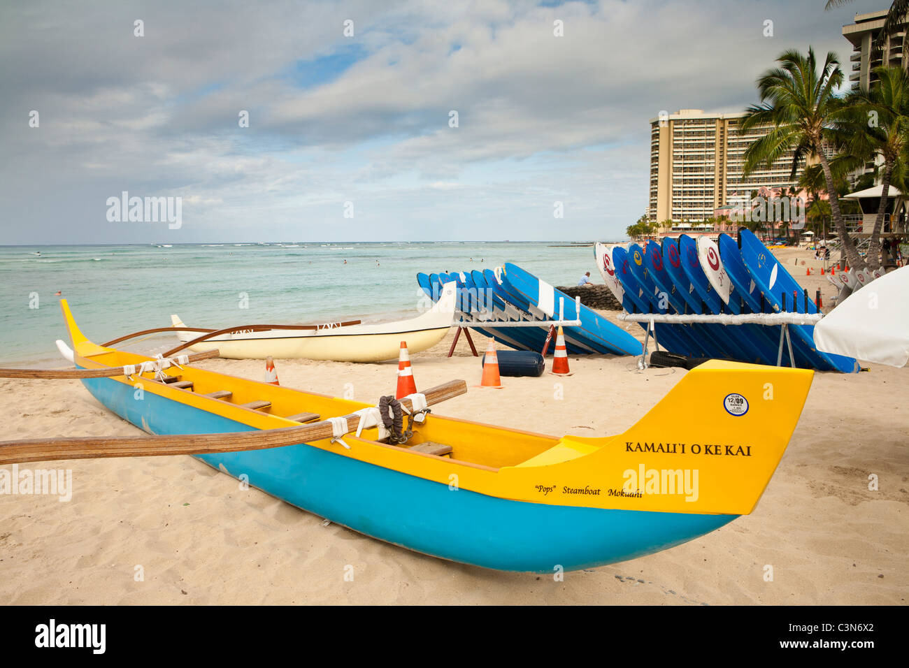 Outrigger canoe and stacked surfboards ready for tourist use in early morning-Waikiki Beach, Honolulu, Oahu, Hawaii, - Stock Image