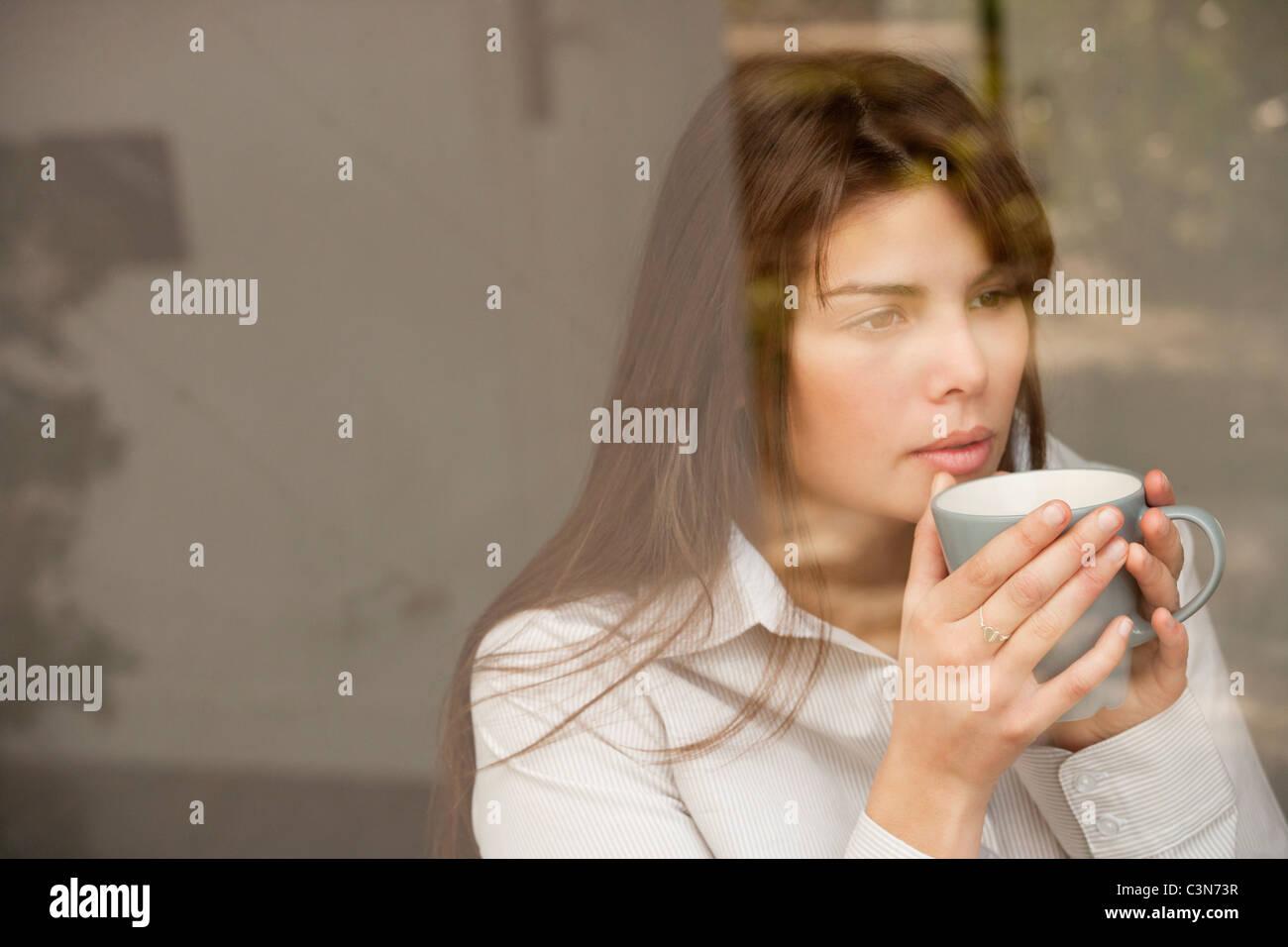 woman drinking tea through a window Stock Photo
