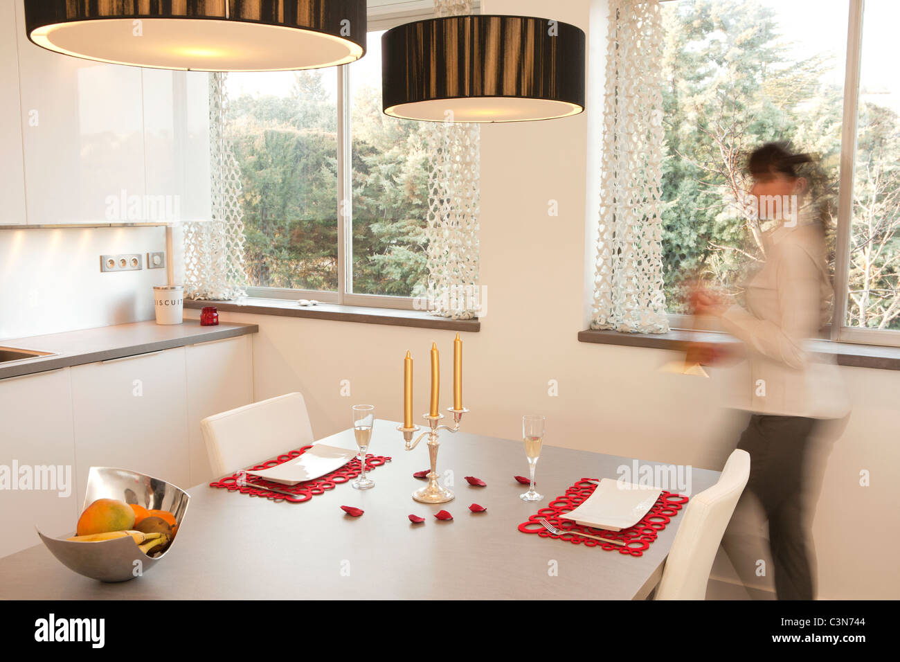 Woman preparing a candle light dinner - Stock Image
