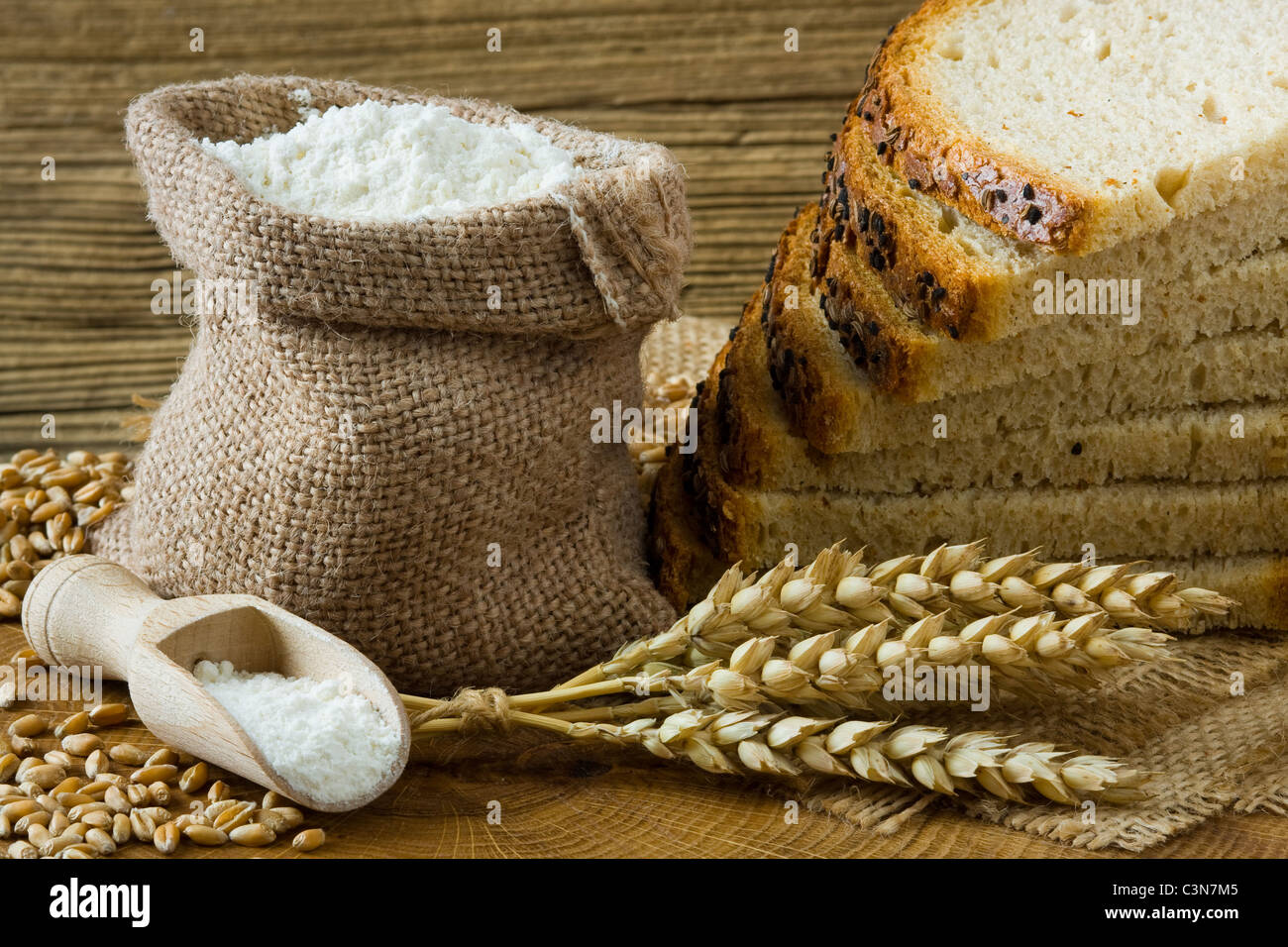 Fresh homemade bread and flour in small burlap bag - Stock Image