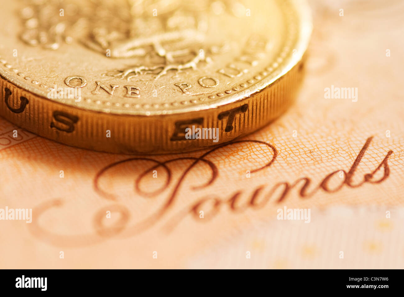 Close up of a British Sterling One Pound Coin on a 10 pound note - Stock Image