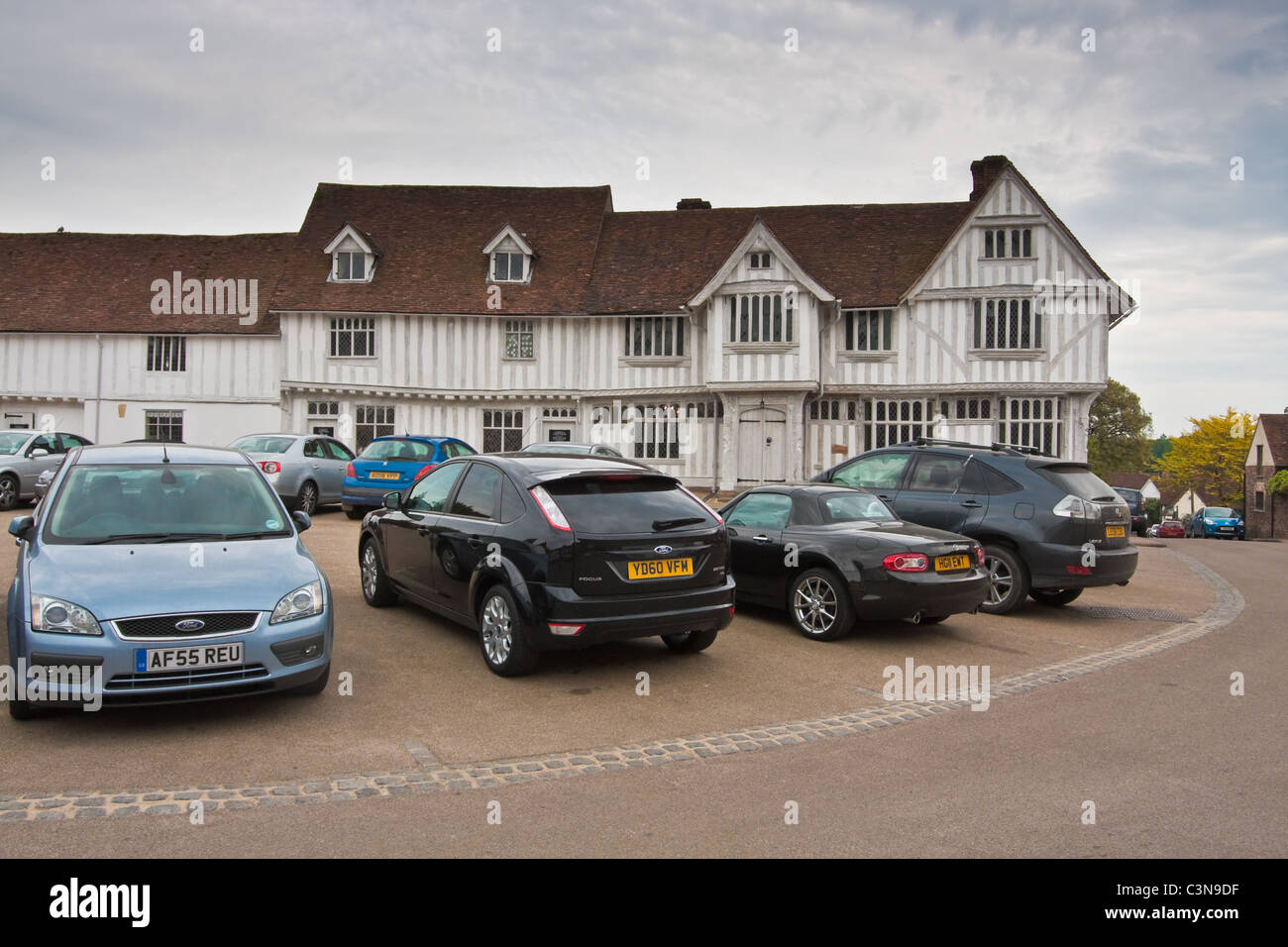 Modern cars parked in front of a medieval building in Lavenham, Suffolk - Stock Image