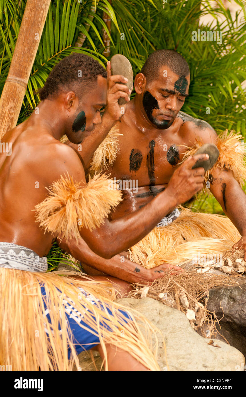 Tradtional Fijian Warriors breaking up coconuts for ceremonial dinner. Castaways Resort, Qalito Island, Mamanucas, - Stock Image