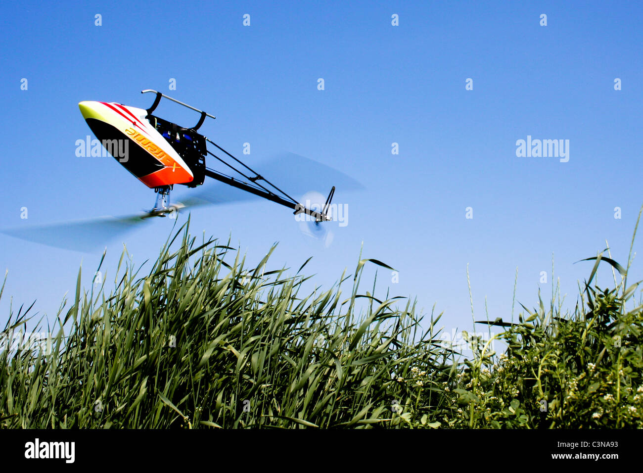 Model helicopter flies inverted over long grass. - Stock Image