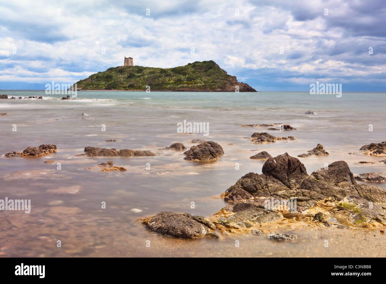 Roman tower on Island Sardinia Italy long exposure milky sea dramatic sky and clouds rocks in surf - Stock Image