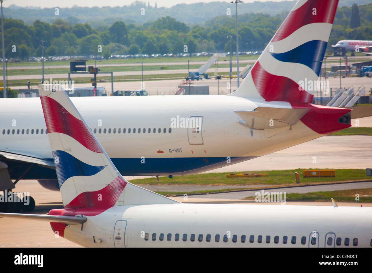 Two British Airways Aeroplanes pass on the tarmac at Gatwick Airport. - Stock Image