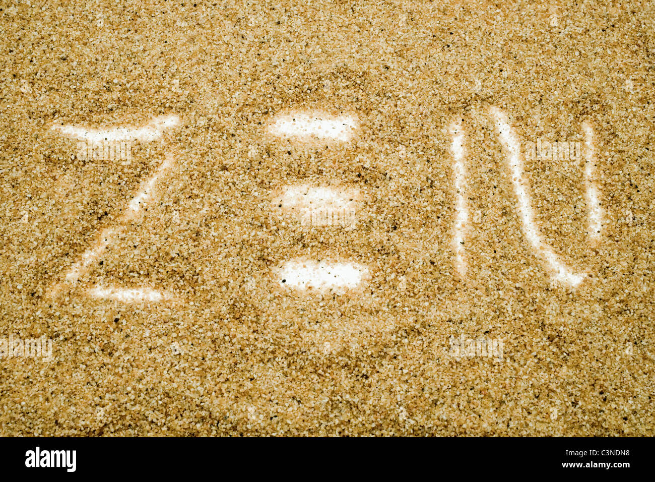 ZEN written with sand in a rock garden isolated over white - Stock Image