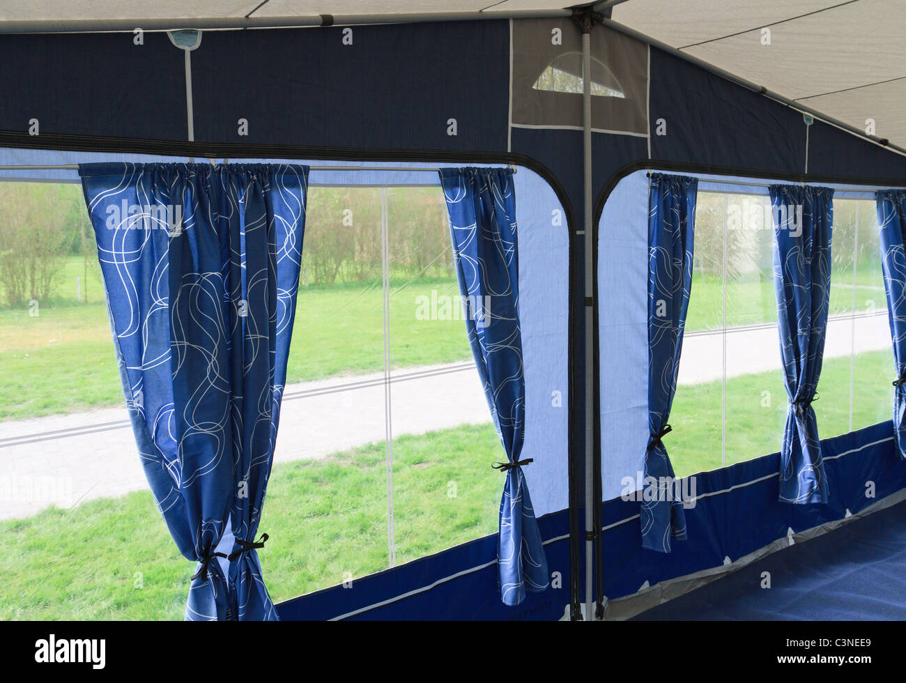 Inside Of Caravan Awning Tent With Blue Curtains And Four Windows