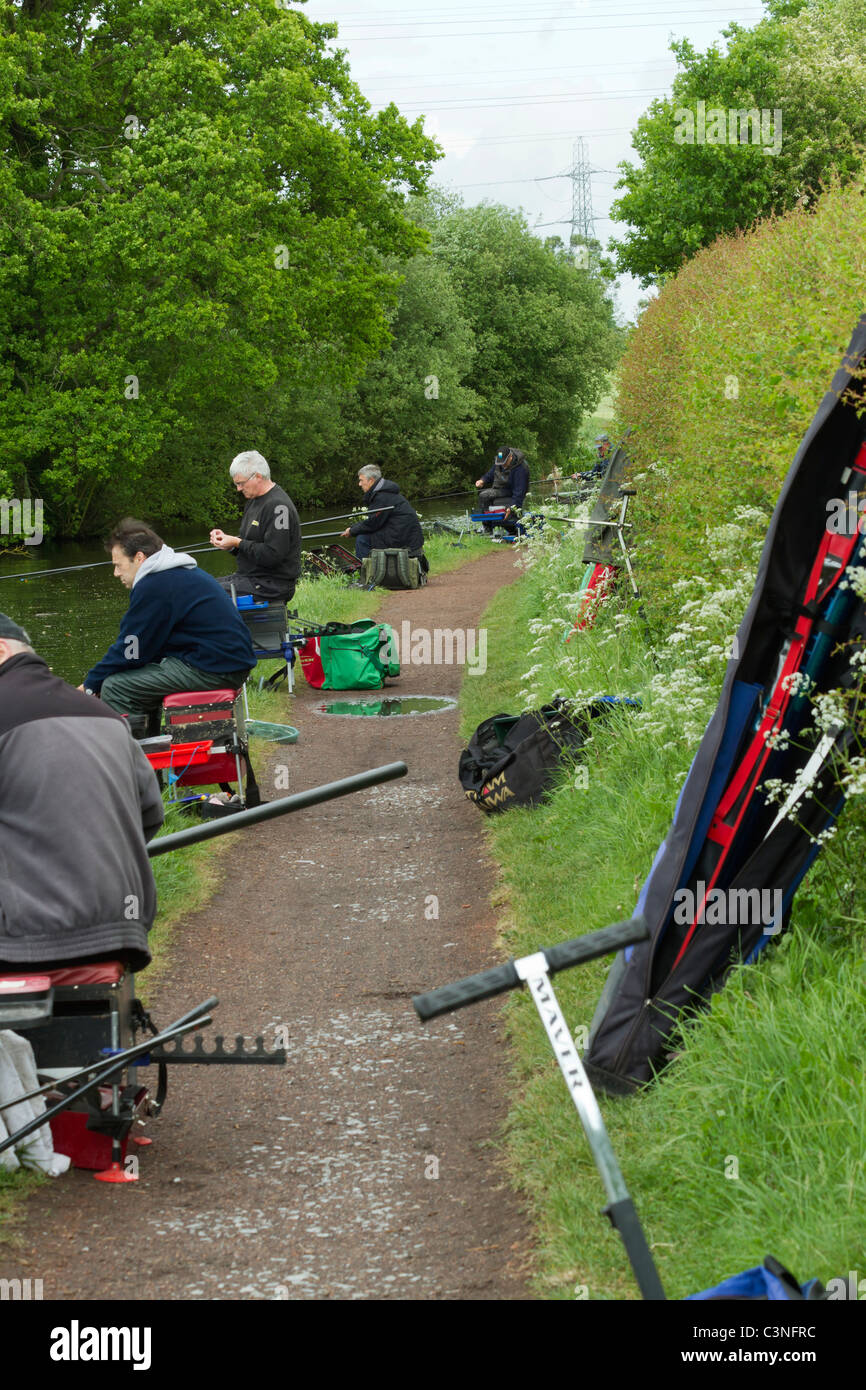 Anglers fishing on a canal towpath - Stock Image