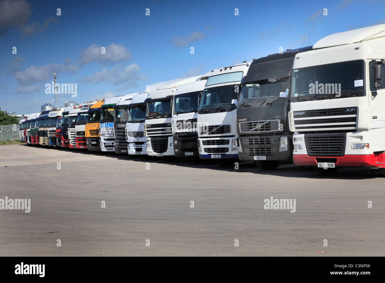 Line up of 2nd hand trucks at truck auction - Stock Image