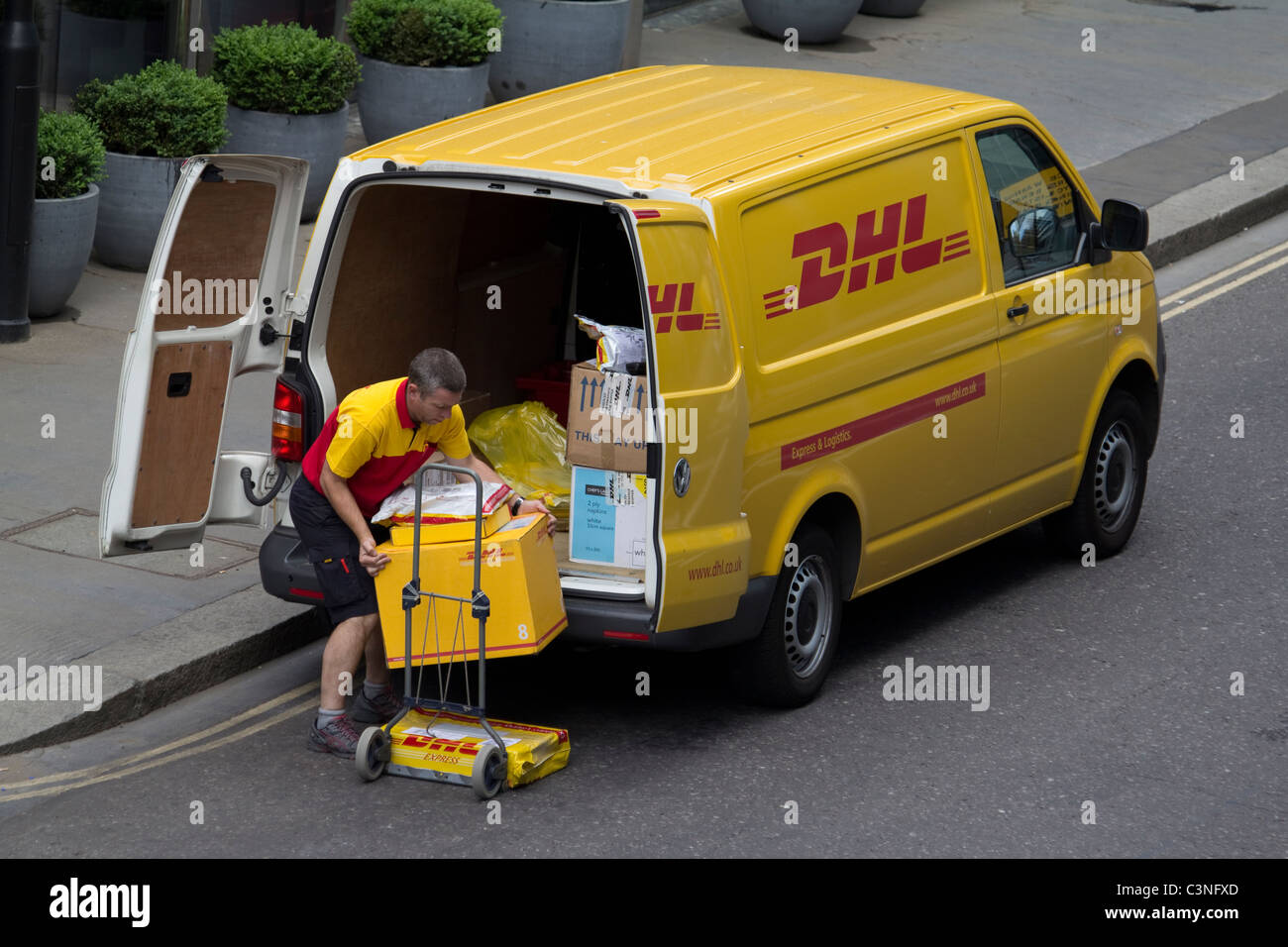 DHL delivery driver unloading van in City of London - Stock Image