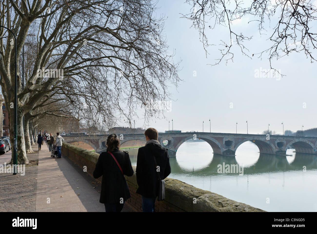 Young couple walking along banks of River Garonne near 16thC Pont Neuf bridge, Toulouse, Haute Garonne, Midi Pyrenees, - Stock Image