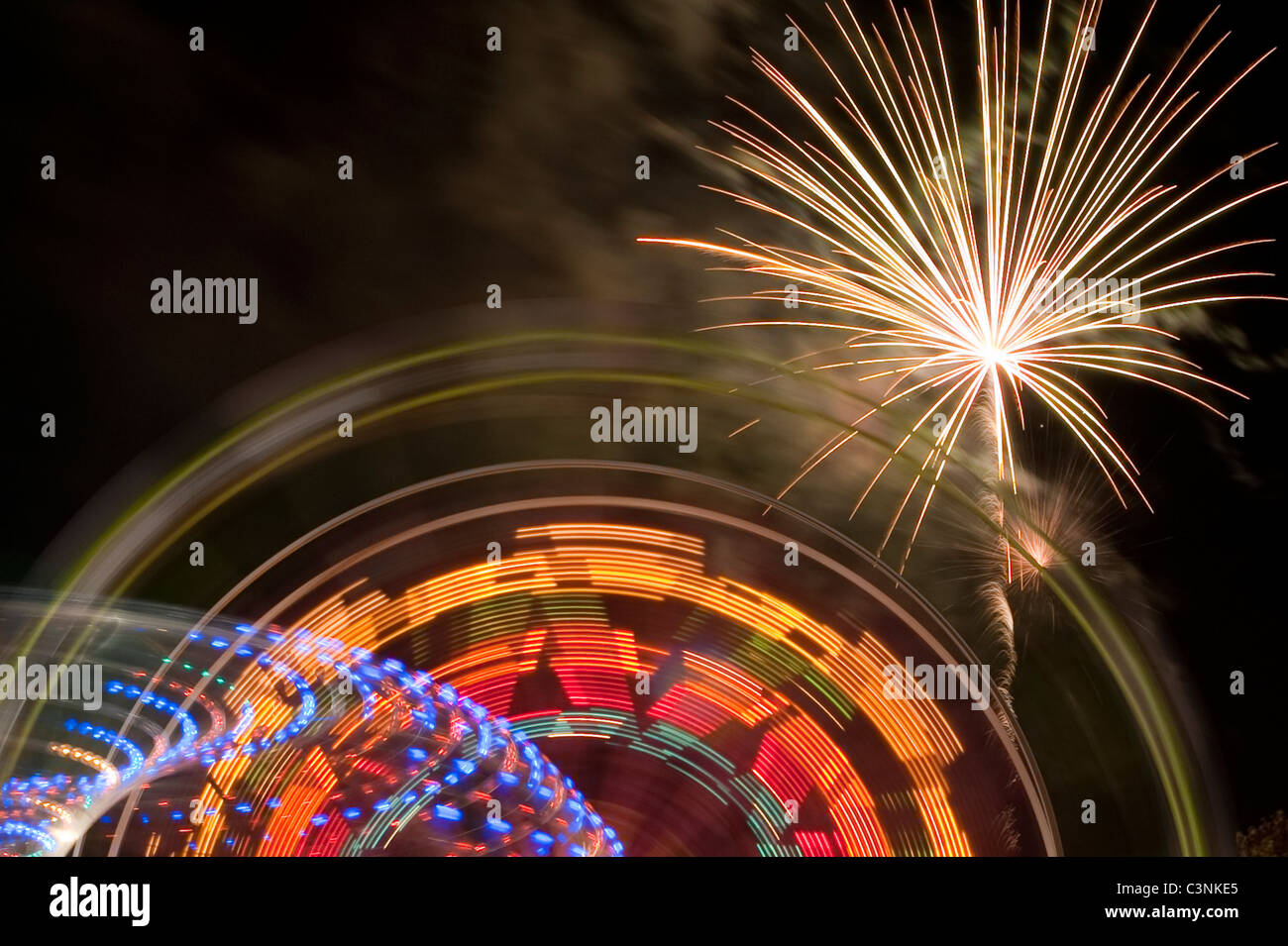 Evergreen State Fair ferris wheel at night with rides and motion with fireworks Snohomish County Monroe Washington - Stock Image