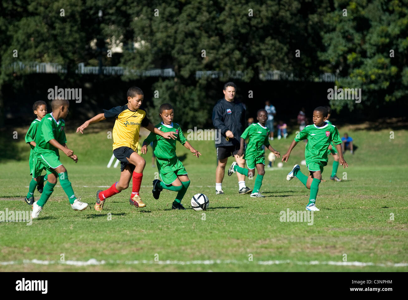 Young football players of an U11 team dribbling referee watching Cape Town South Africa - Stock Image