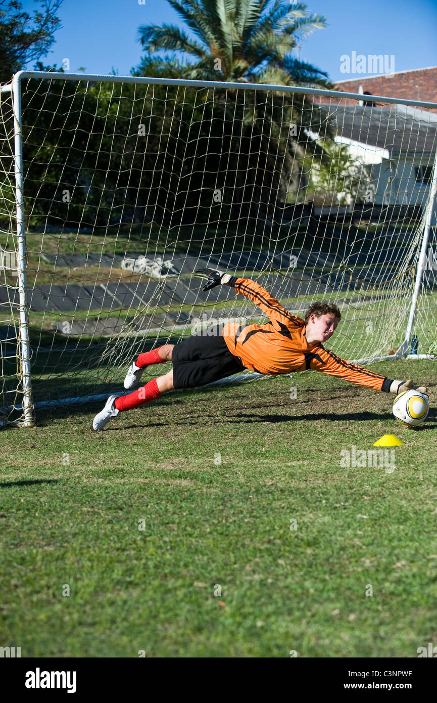 Goalkeeper of an U13 football team saving a ball Cape Town South Africa - Stock Image