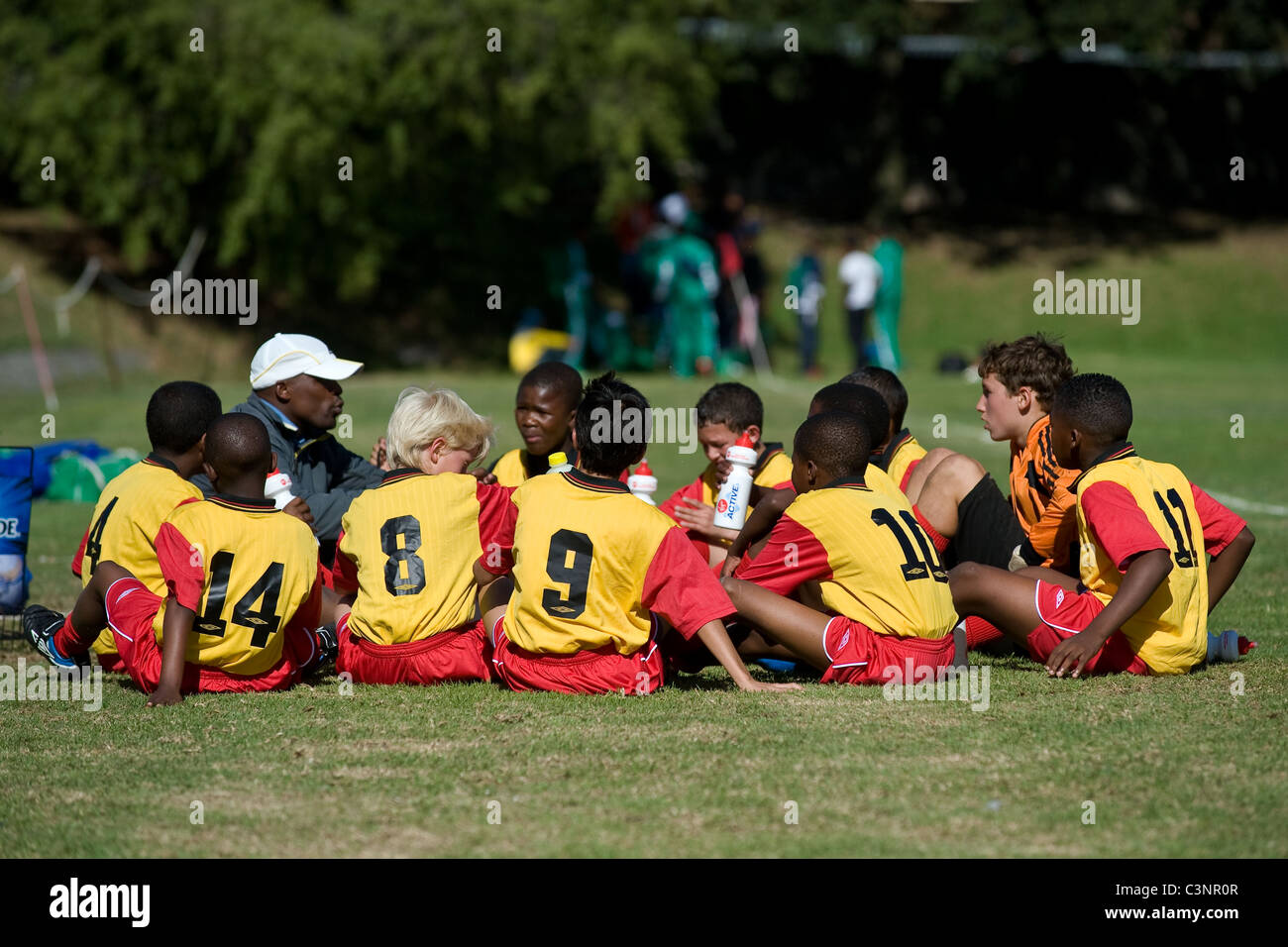 Coach intstructing U13 football players during half-time break Cape Town South of an Africa - Stock Image