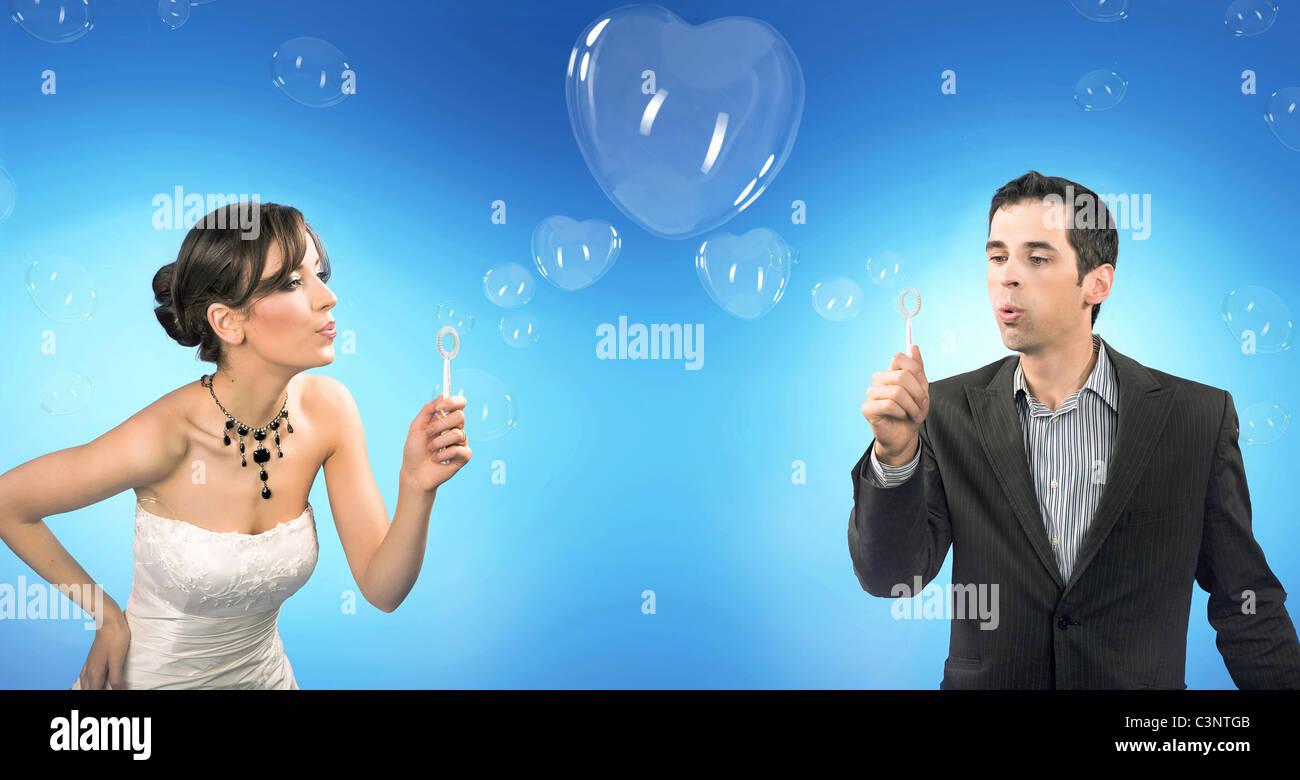 Wedding couple blowing heart shaped romantic soap bubbles - Stock Image