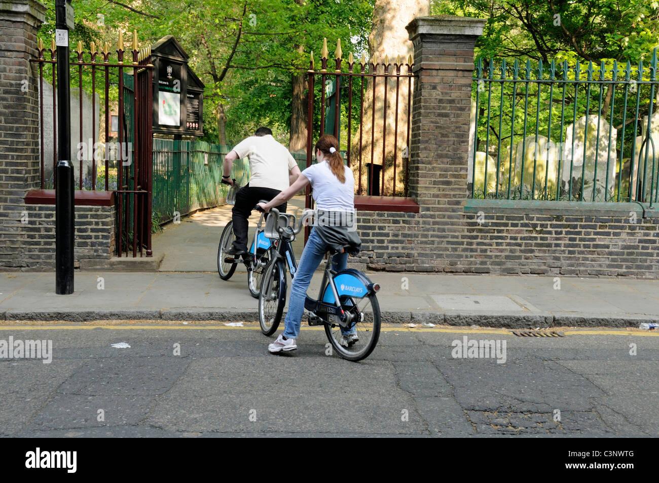 People on Barclay's bikes entering Bunhill Fields London UK - Stock Image