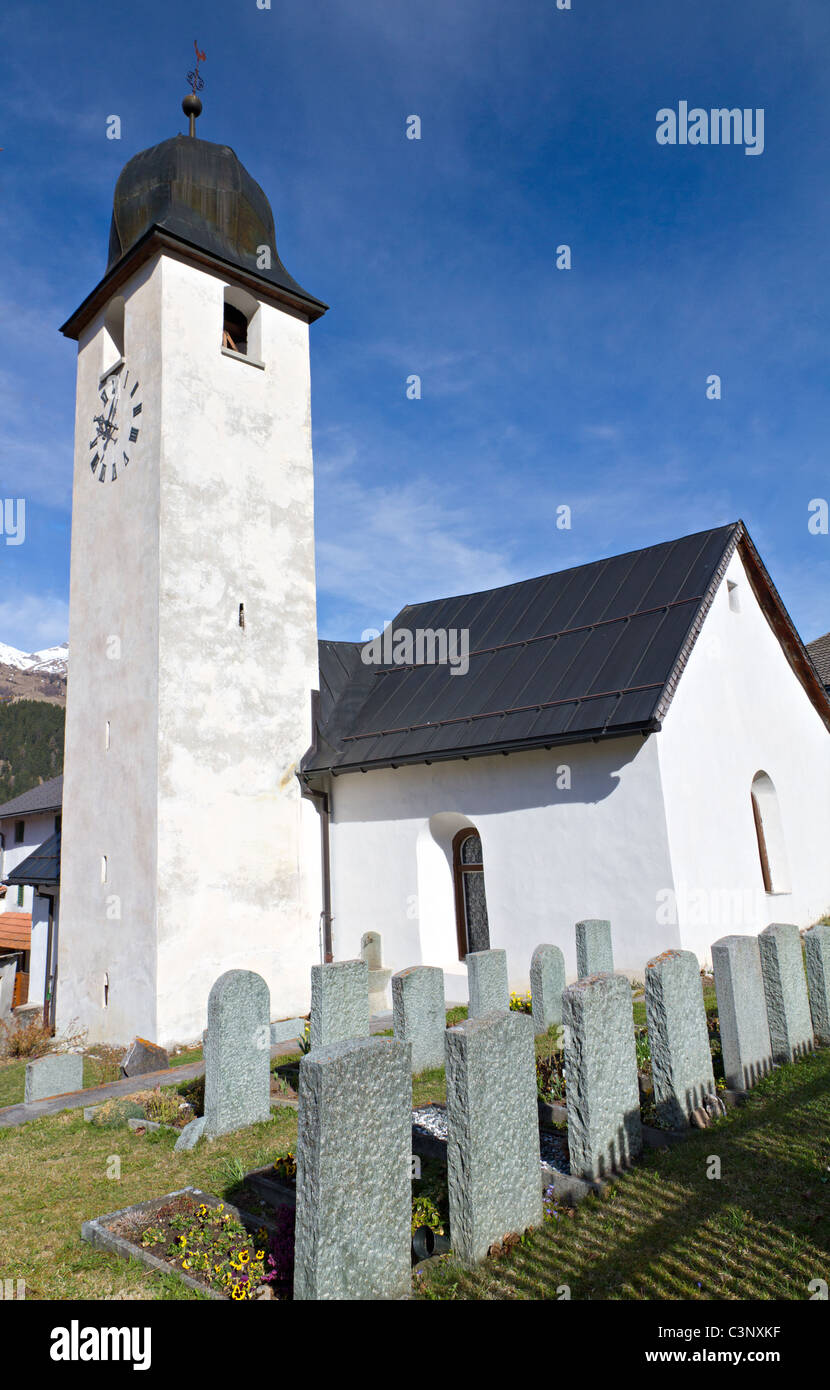white classic village church with cemetery, in Andeer Graubuenden, Switzerland - Stock Image