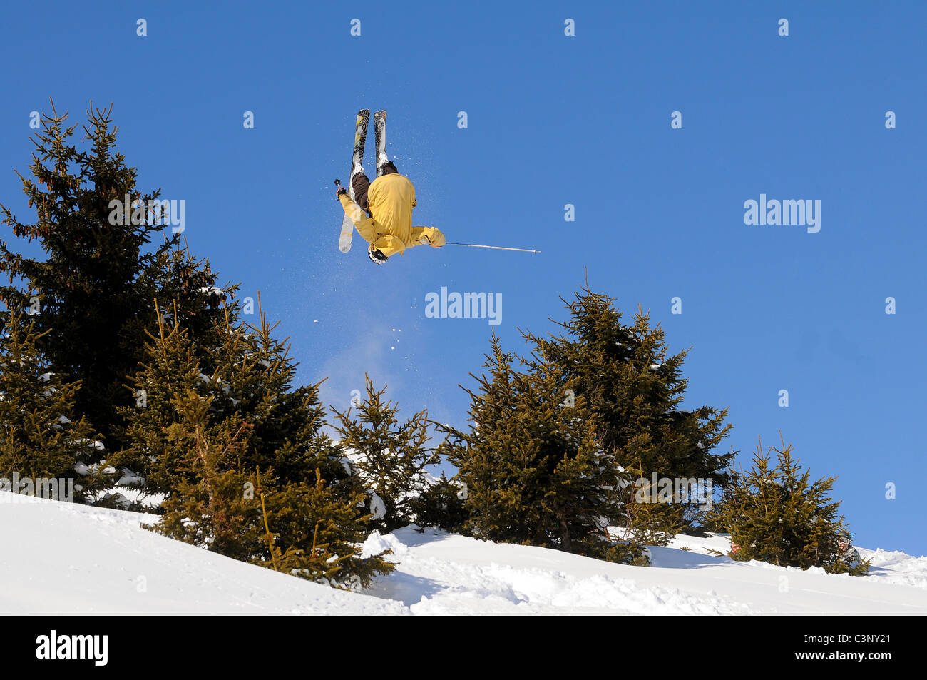 A skier performs a front flip off a huge jump in the ski resort of Courchevel in the French alps. - Stock Image