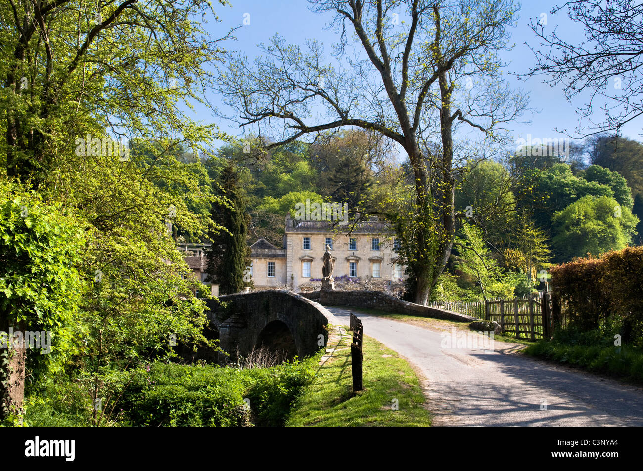 Picturesque scene at Iford of single track road, bridge and Iford manor, taken at Iford, Bradford on avon on fine Stock Photo