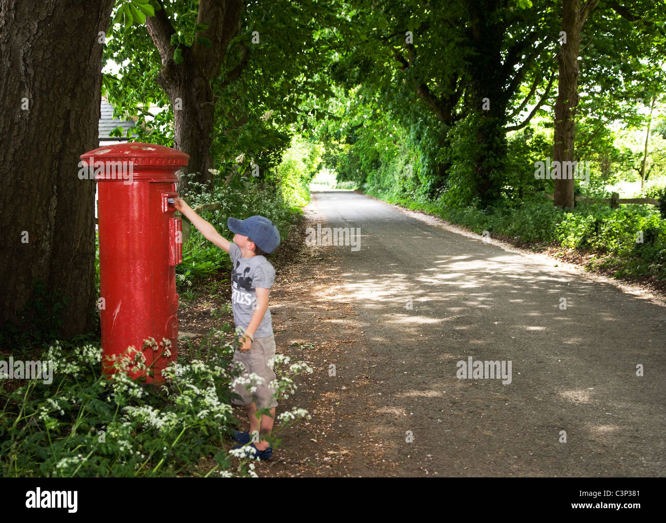 Child posting a letter in a country lane - Stock Image