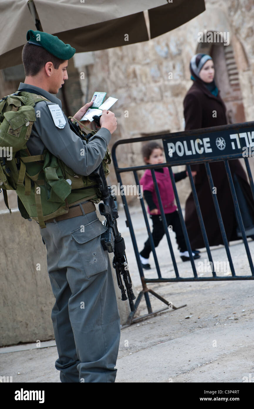 An Israeli soldier examines ID cards at a military checkpoint controlling movement along Shuhada Street. - Stock Image