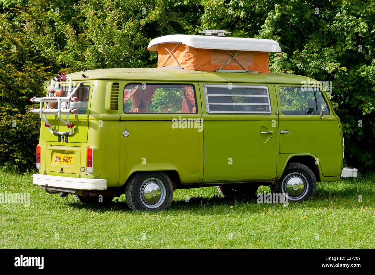 Lime green VW camper van parked in a field. UK - Stock Image