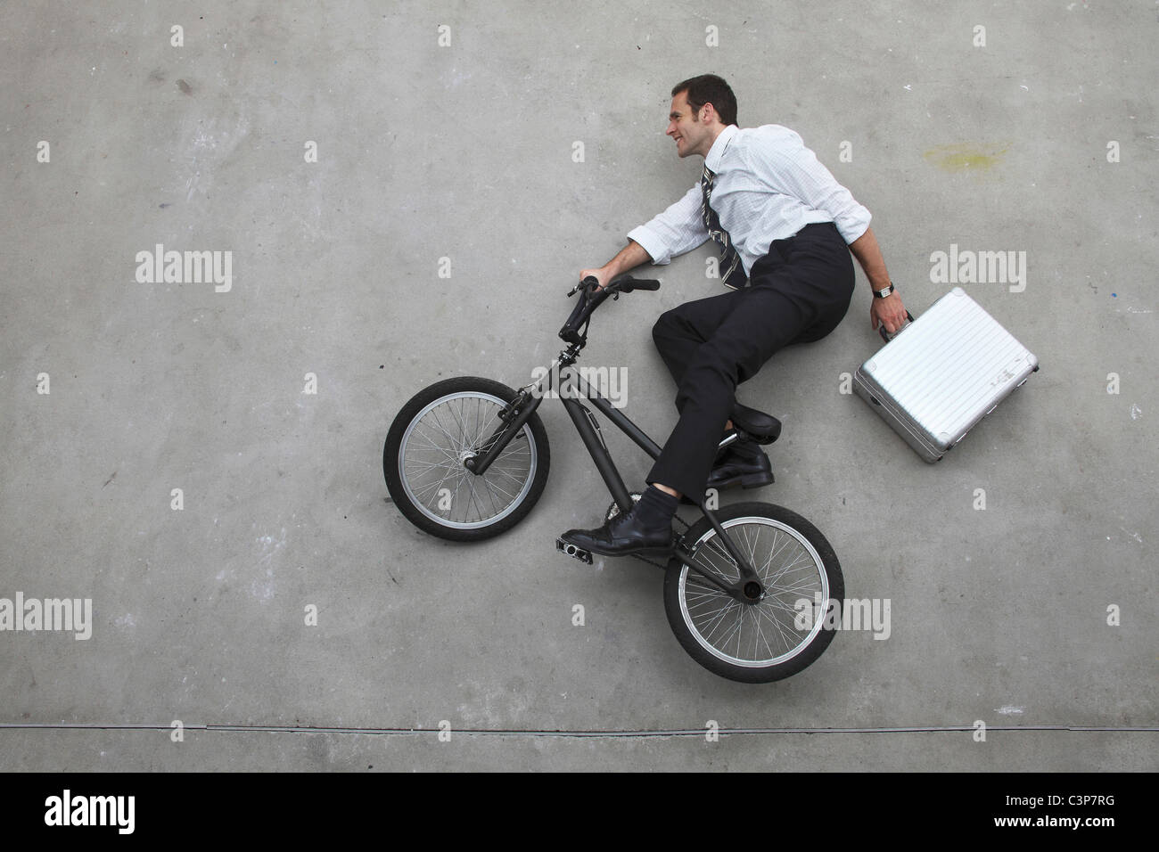 Businessman riding bicycle holding suitcase, elevated view - Stock Image