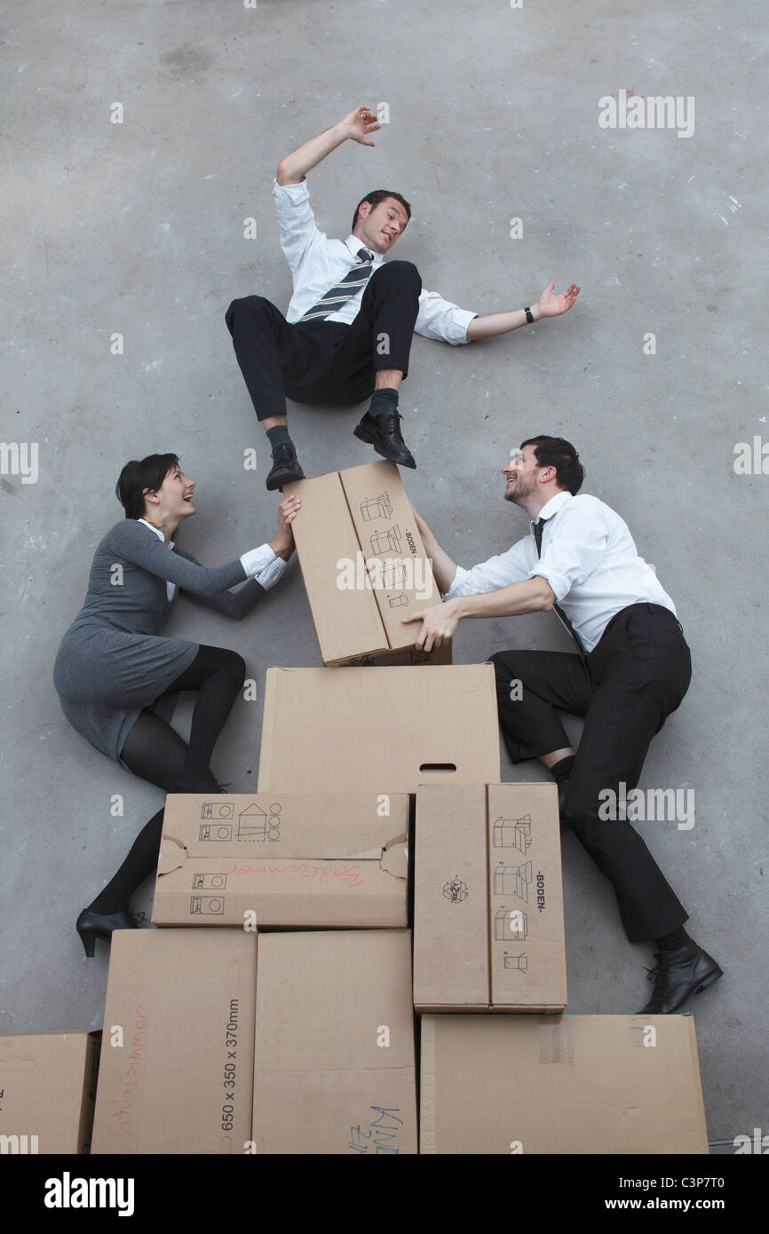 Three business people balancing on cardboard boxes, smiling, portrait, elevated view - Stock Image