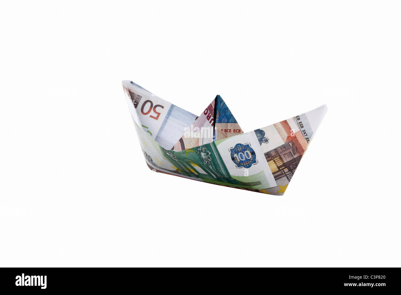 Origami paper boat of euro notes on white background - Stock Image