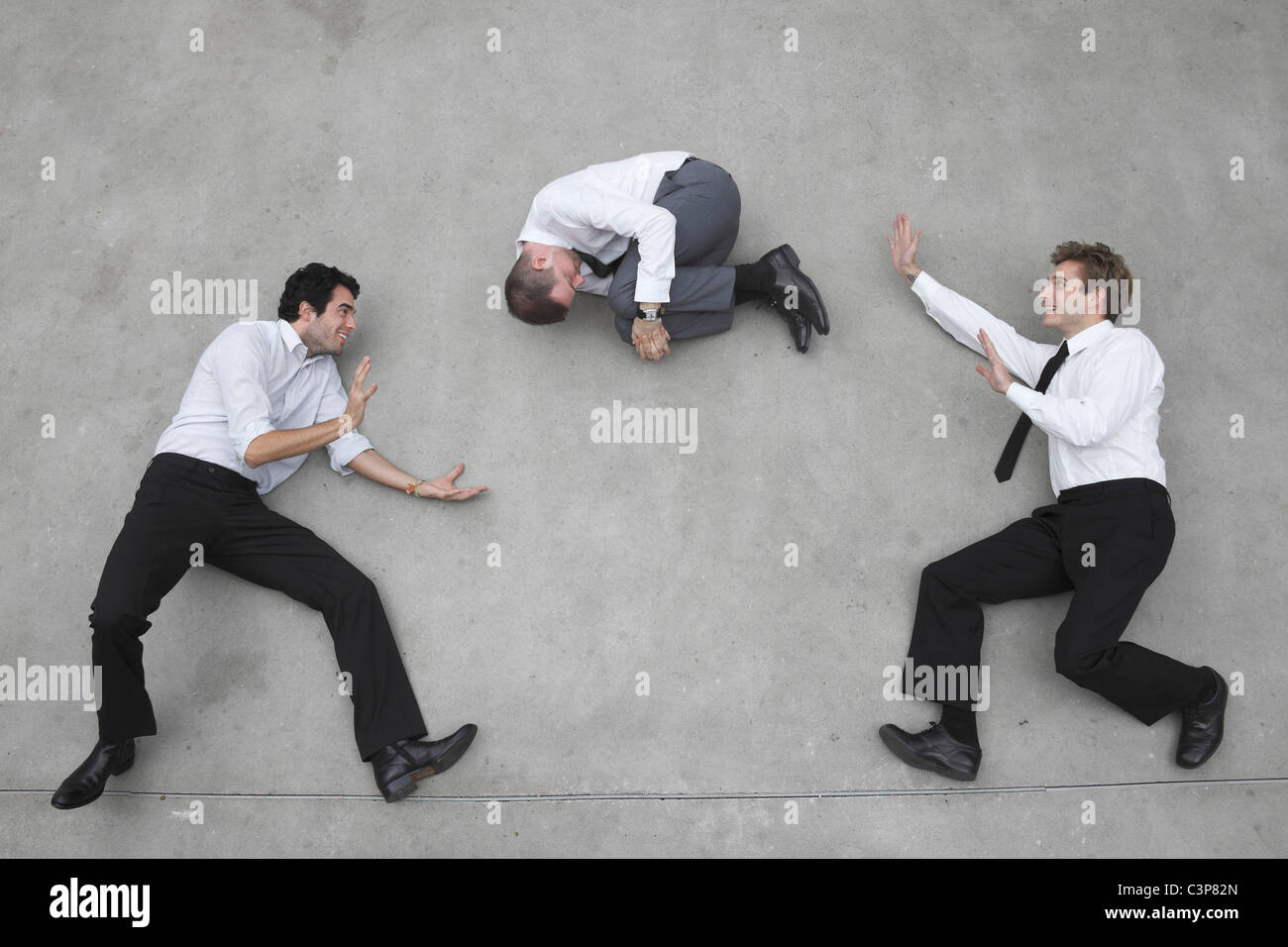 Businessmen balancing on rope,playing with collegue - Stock Image