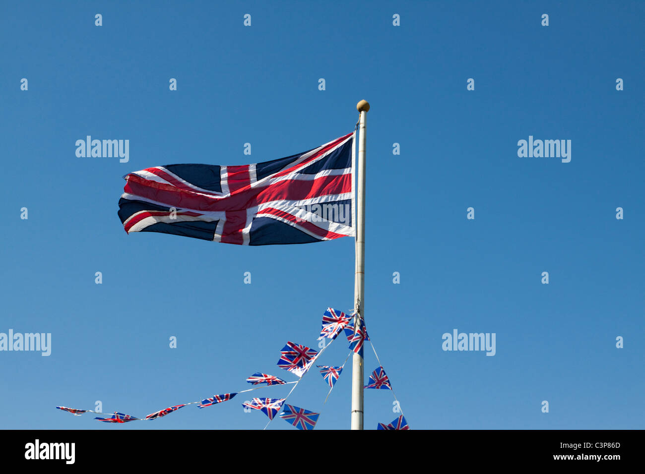 Union Jack flying from a flag pole - Stock Image