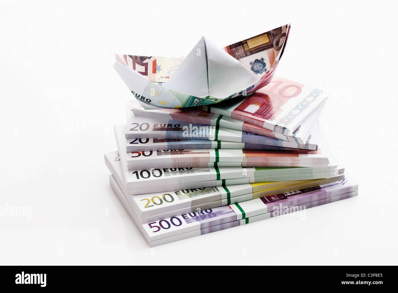 Euro paper boat on bundles of euro notes, close-up - Stock Image