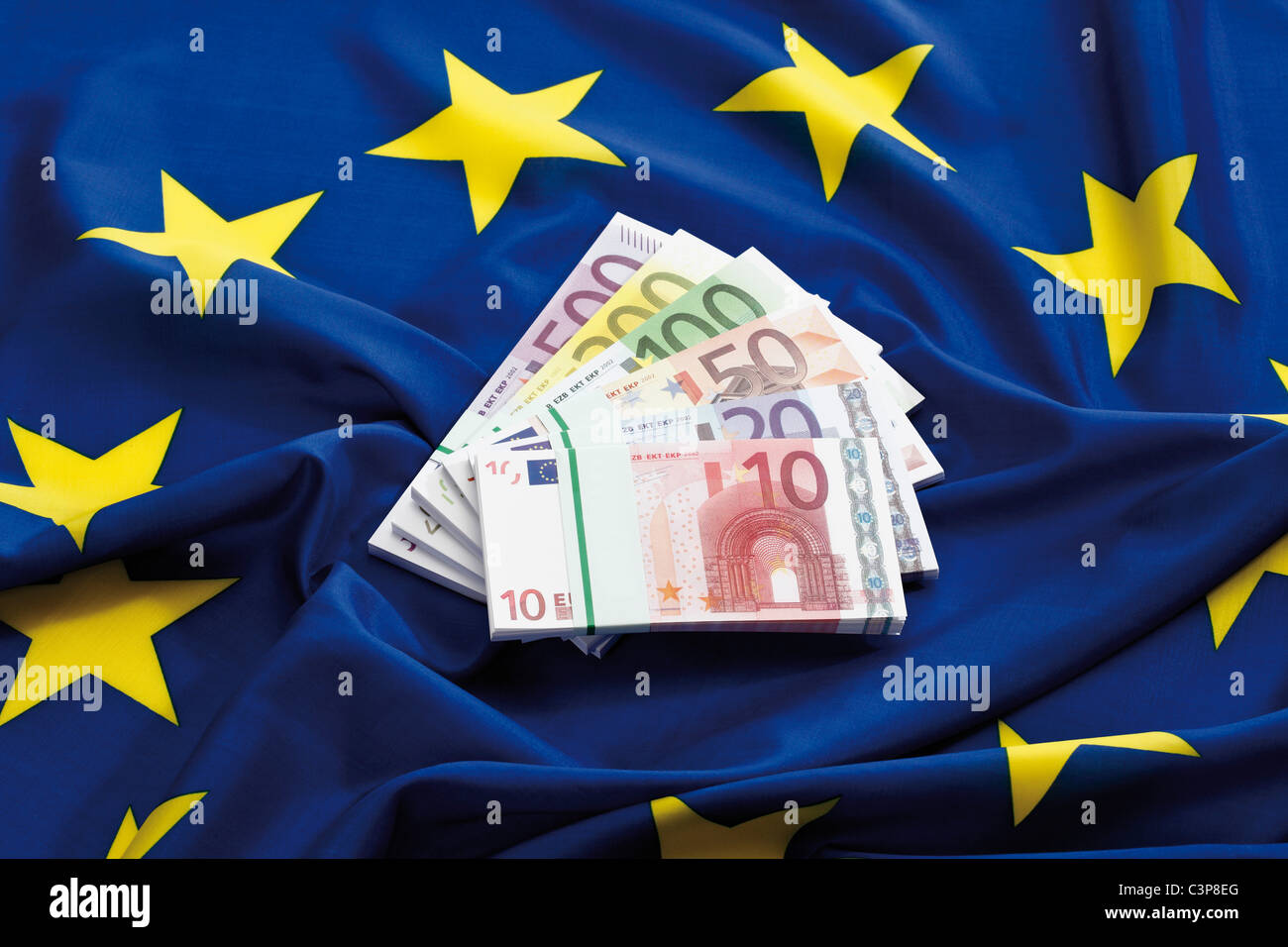 Euro notes fanned out on european union flag - Stock Image