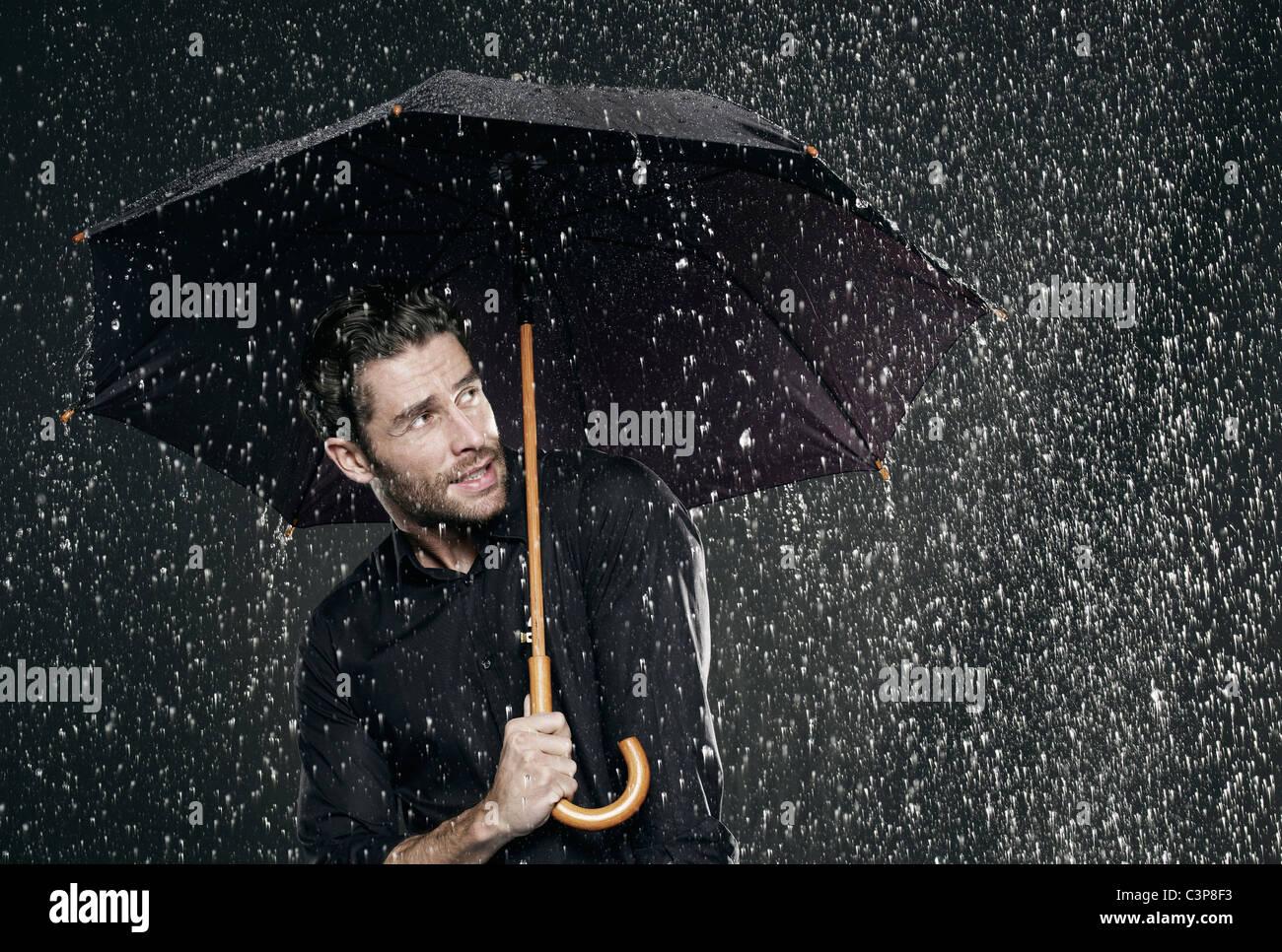 man holding umbrella in rain looking away stock photo 36754343 alamy