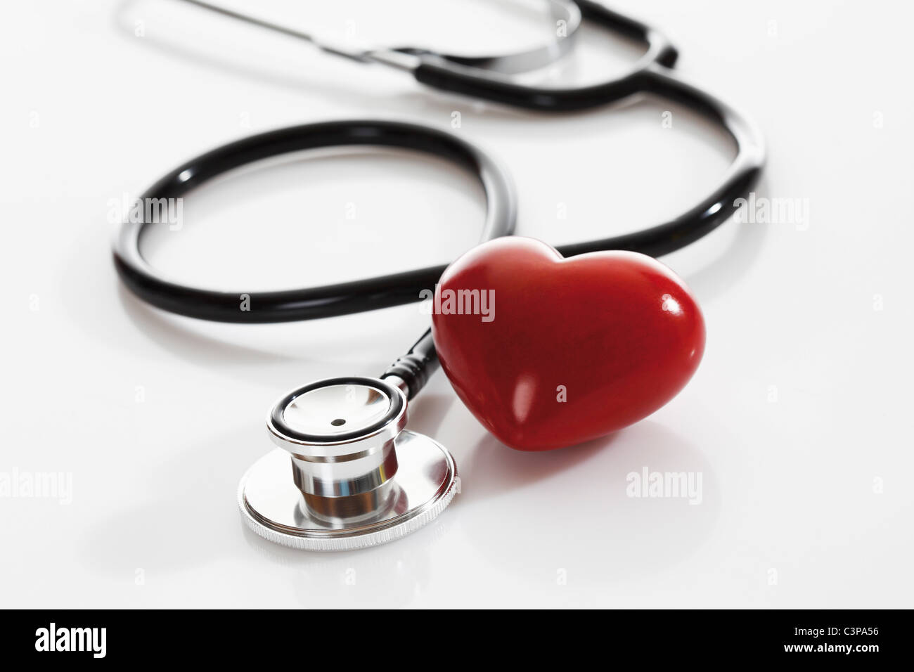 Stethoscope with heart shape object on white background, close up - Stock Image