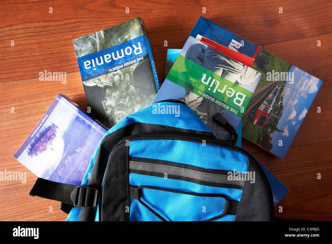 various travel guide books falling out of a backpack - Stock Image