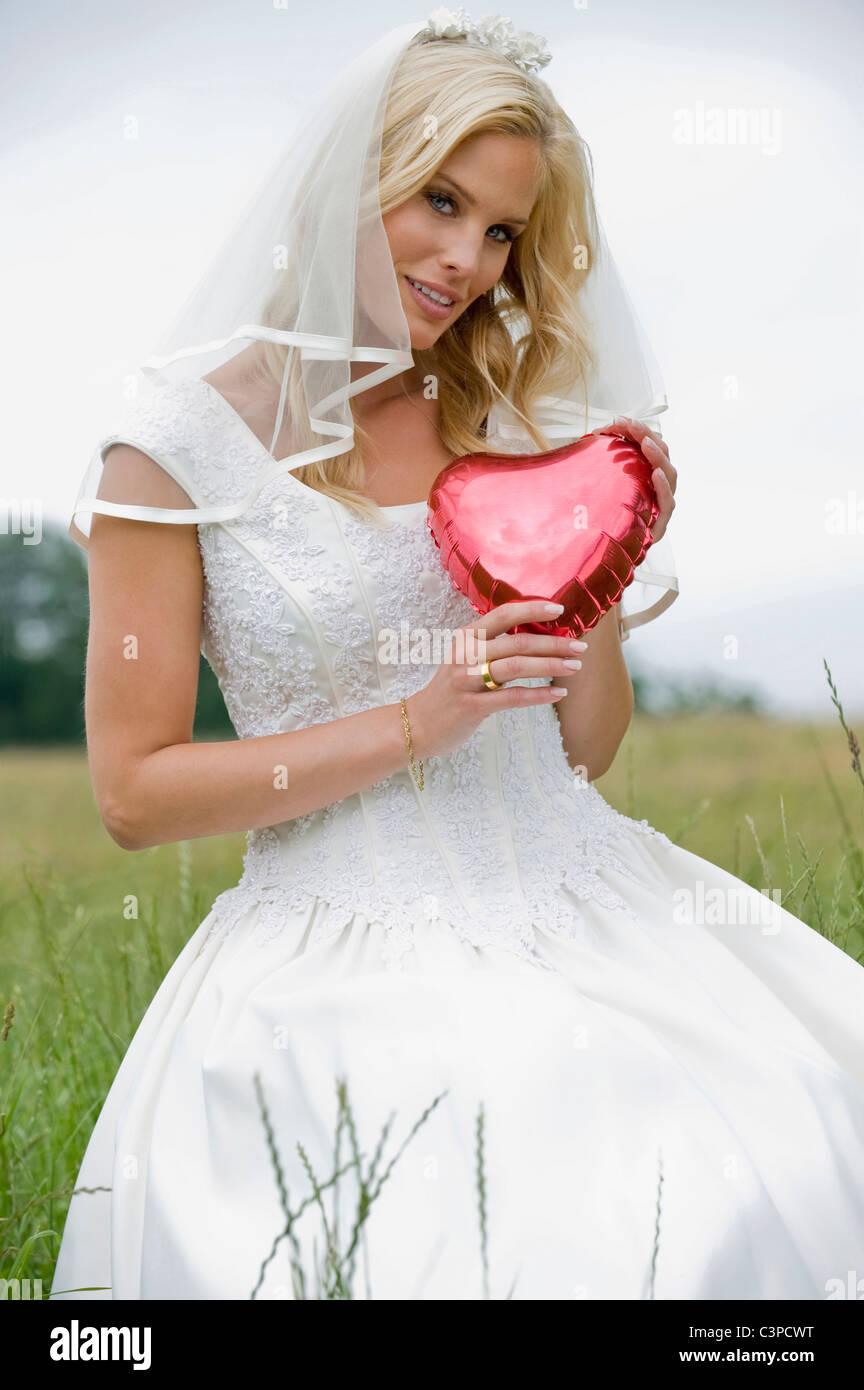 Bride holding heart shape object, smiling. - Stock Image