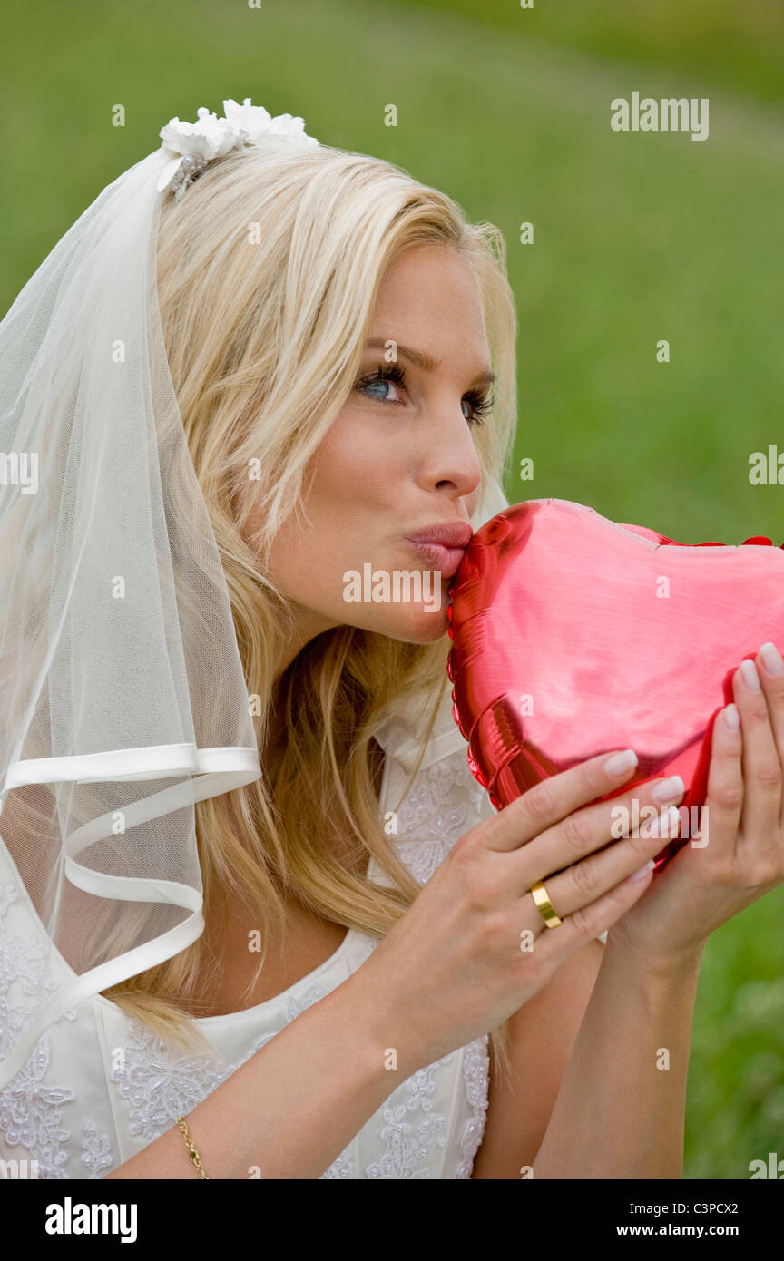 Bride holding heart shape object, smiling, looking away. - Stock Image