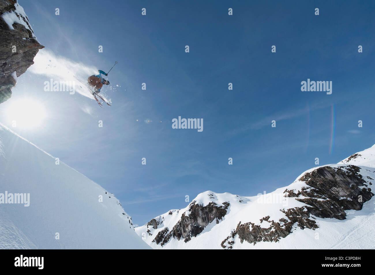 Austria, Arlberg, Man skiing downhill, doing jump, low angle view - Stock Image