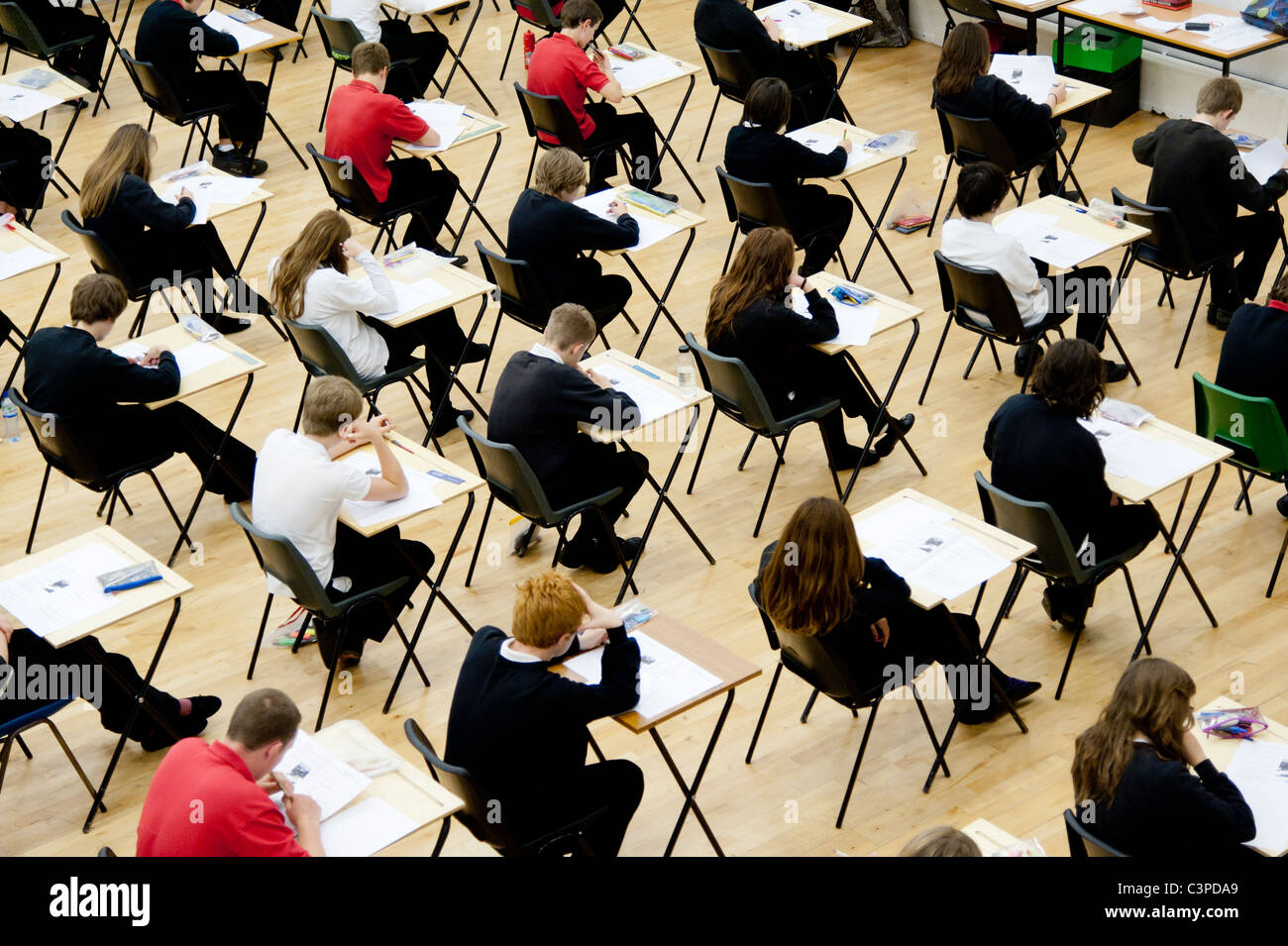 Rows of teenage boy and girl school students sitting their GCSE examinations, UK - Stock Image