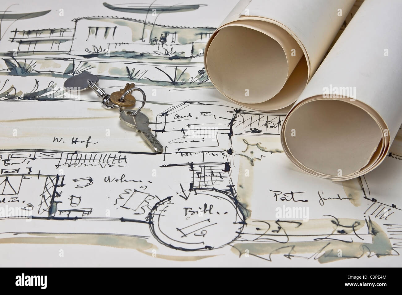 the blueprint of a house with two paper rolls and the keys for the new house - Stock Image