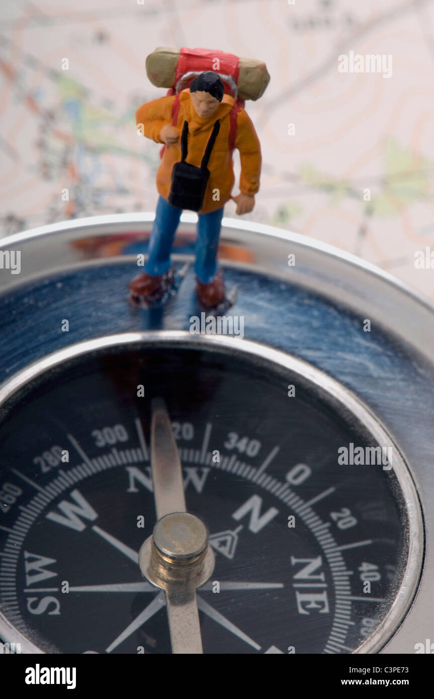 Traveller miniature standing on compass - Stock Image