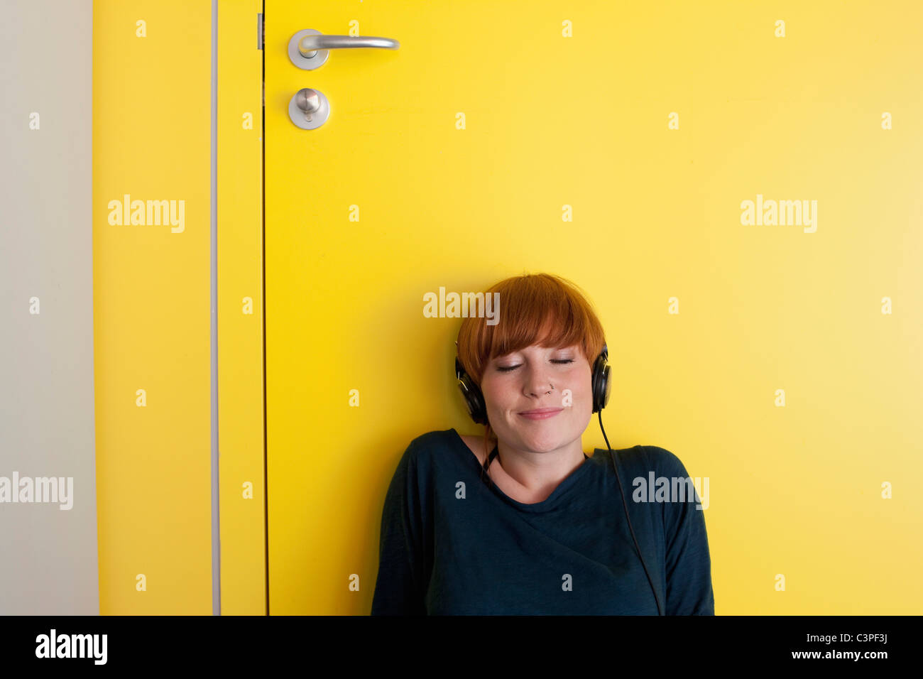 Germany, Leipzig, Young woman sitting and listening music in locker room - Stock Image