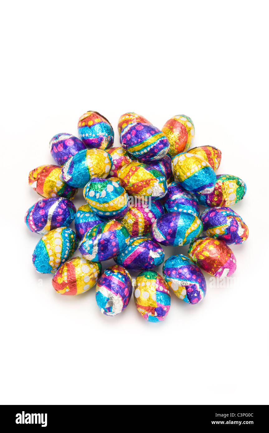 Easter eggs wrapped in foil on white - Stock Image