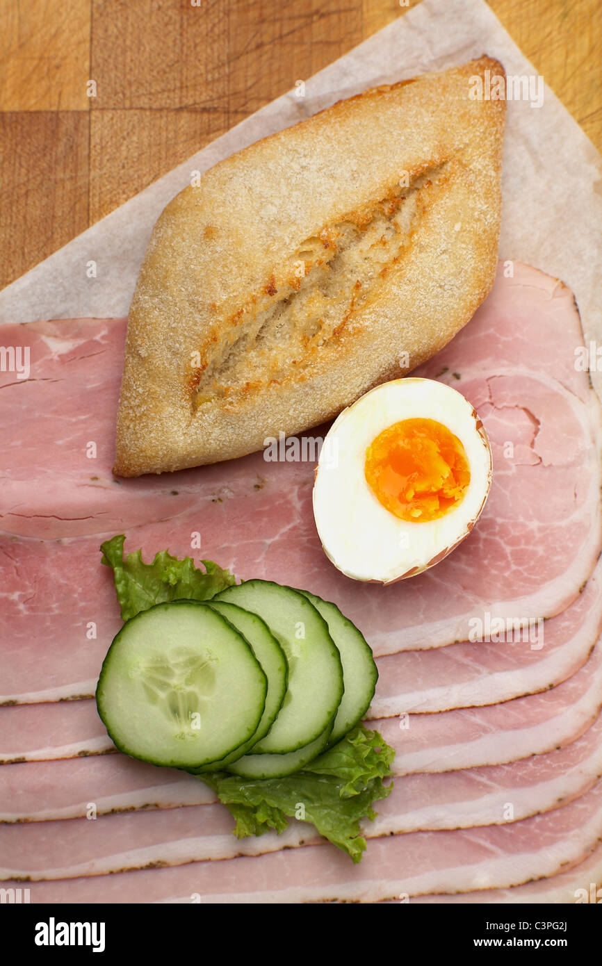 Bread roll, cucumber slices, egg and cooked ham, elevated view - Stock Image
