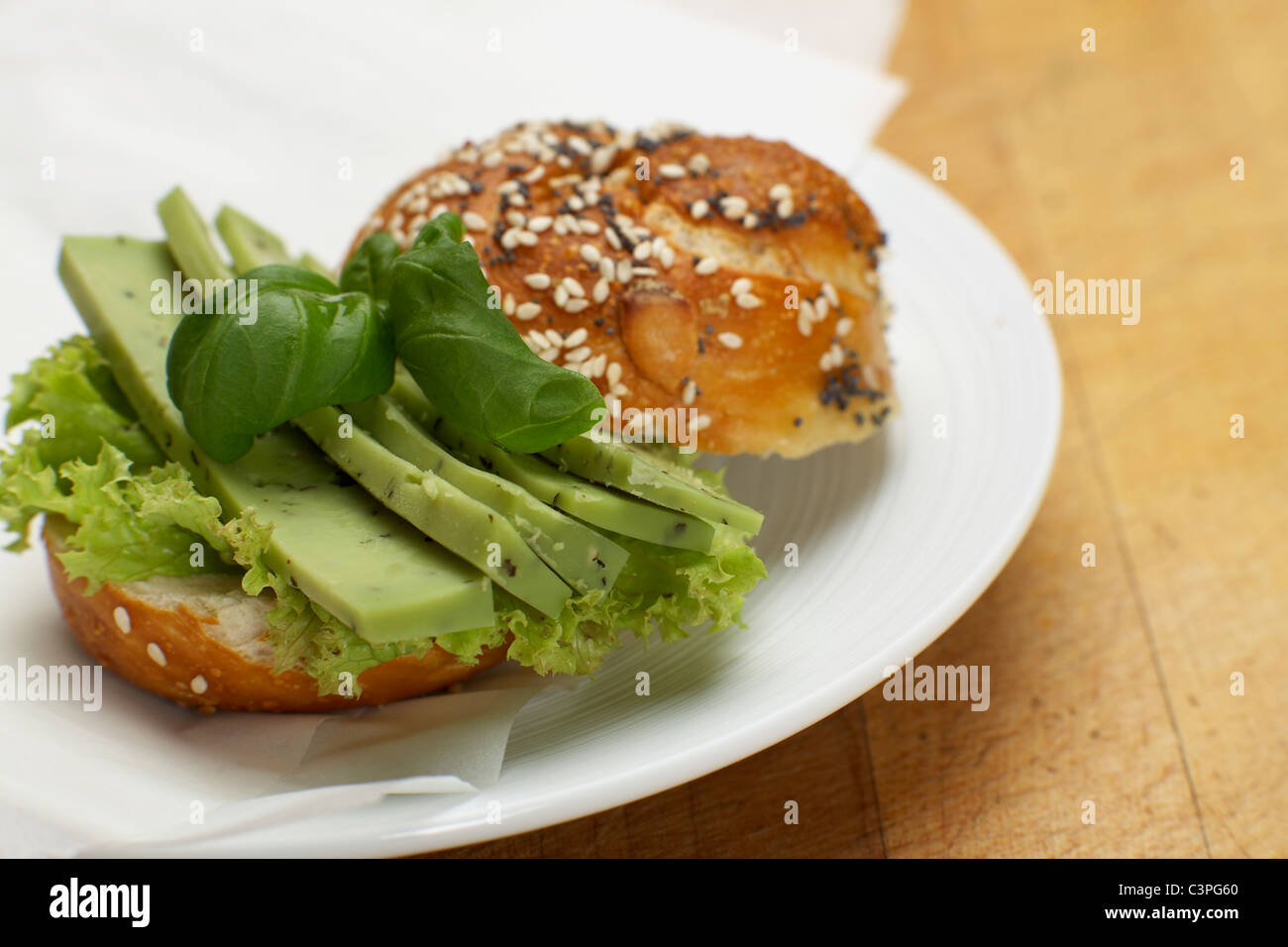 Cheese roll sandwich with basil, pest and salad on plate - Stock Image