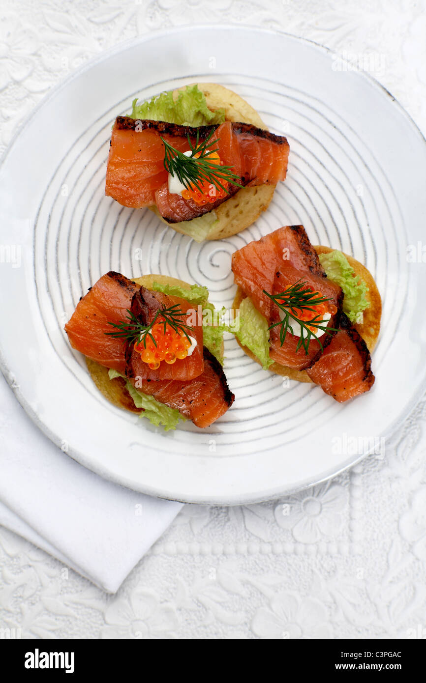 Appetiser, Canapes with salmon, dill and trout caviar on plate, elevated view - Stock Image
