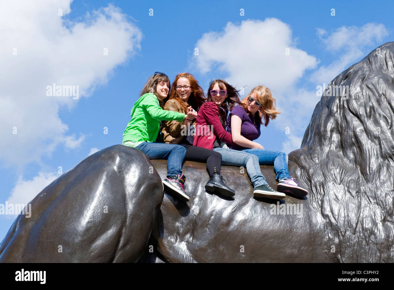 London , Westminster , Trafalgar Square , 4 or four pretty young girls pose for photo or photograph  astride statue - Stock Image